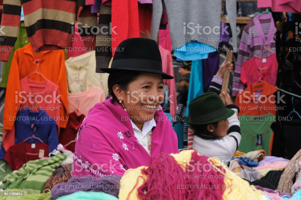 the smiling woman in the traditional dress is selling clothes stock photo