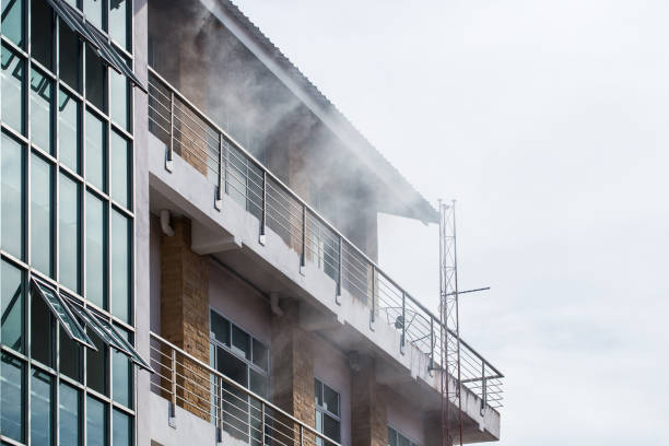 The smoke coming out of the front of the high building due to a fire. stock photo