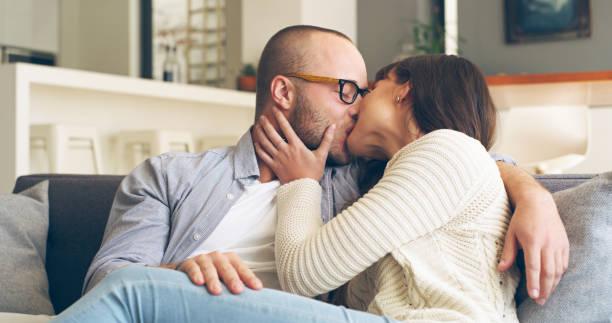 the smooch of love - brunette woman eyeglasses kiss man foto e immagini stock