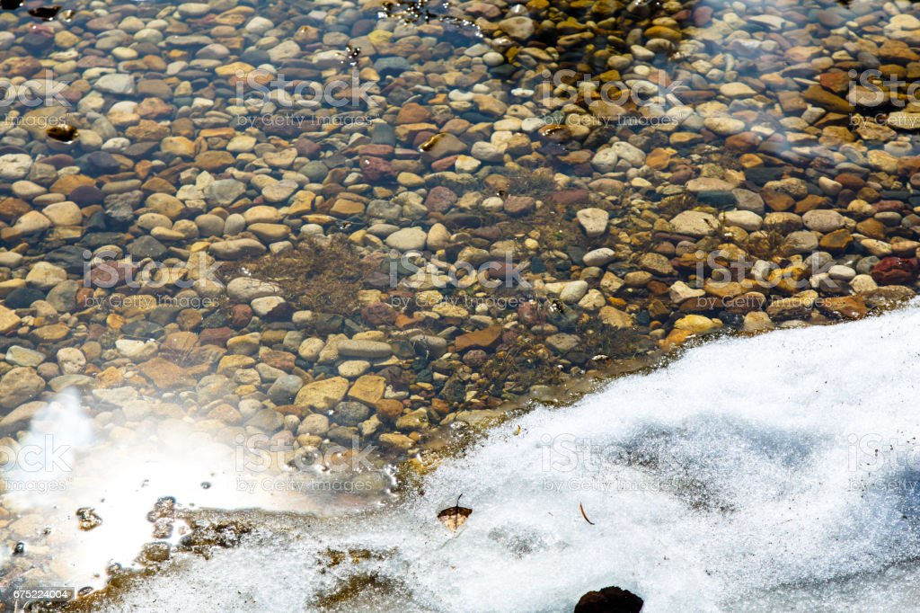 The snow is melting on the banks of puddles. The bottom of colored pebbles in a shallow puddle. royalty-free stock photo