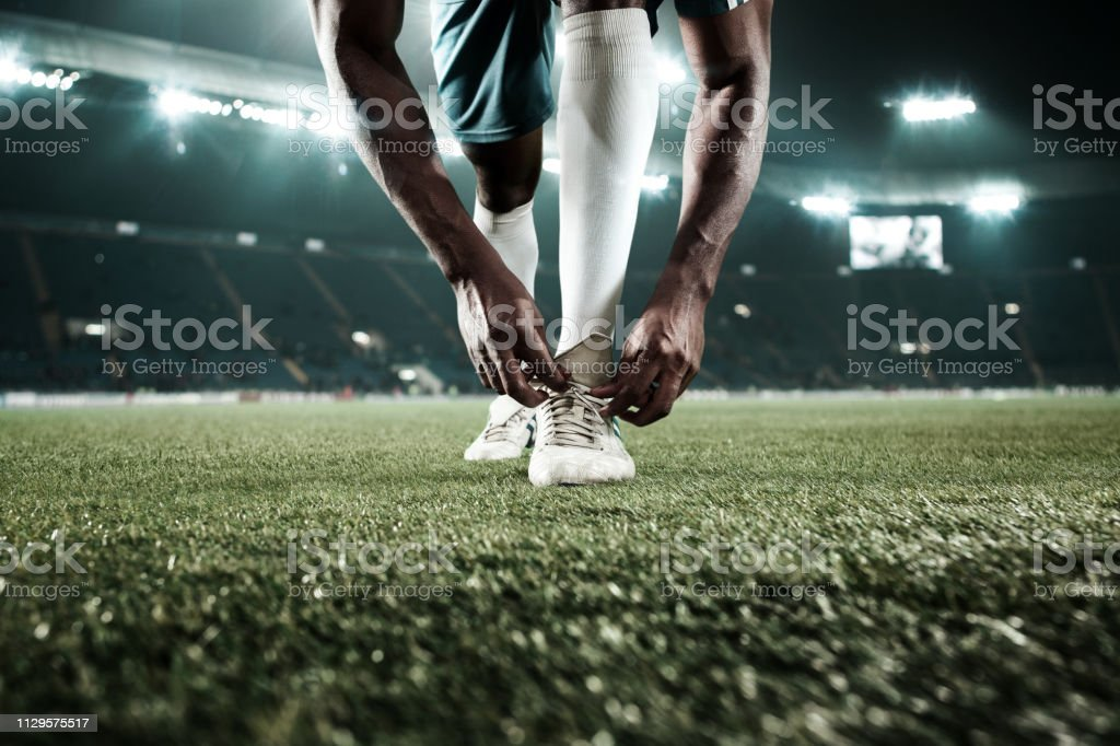 The soccer player kicking the ball at stadium stock photo
