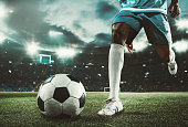 Soccer player kicking the ball at the stadium. The stadium is made in 3D.