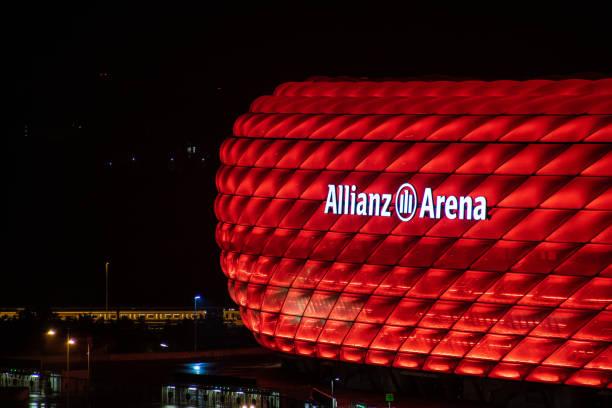das fußballstadion (allianz arena) in münchen des teams fc bayern münchen in der nacht in roten farben - bayern fußball heute stock-fotos und bilder