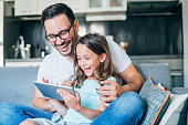 Young father and his cute small daughter having fun with digital tablet on couch.