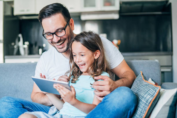 The sofa is our happy Young father and his cute small daughter having fun with digital tablet on couch. leisure games stock pictures, royalty-free photos & images