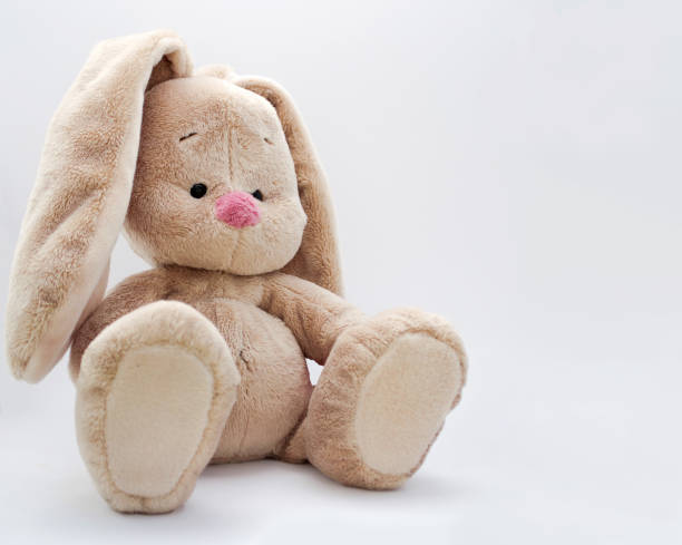 The soft toy bunny sits on a bright background a cute baby soft toy bunny sitting on a bright background fluffy stock pictures, royalty-free photos & images