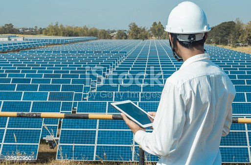 The solar farm(solar panel) with engineers walk to check the operation of the system by laptop, Alternative energy to conserve the world's energy, Photovoltaic module idea for clean energy production.