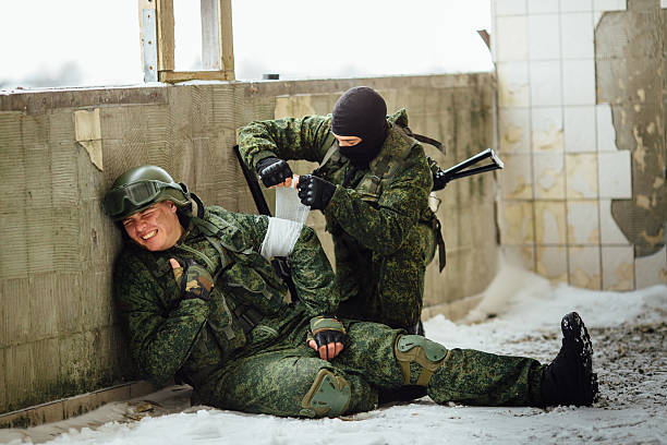 The soldier bandaging his friend in a combat situation. stock photo