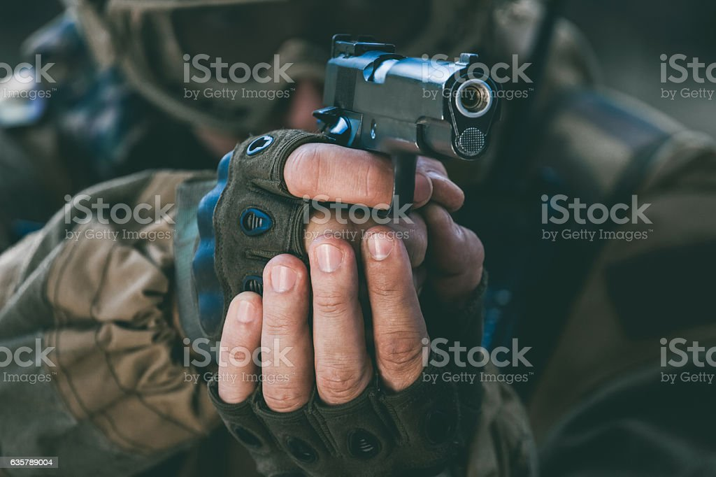 the soldier holding pistol takes aim for shot. stock photo