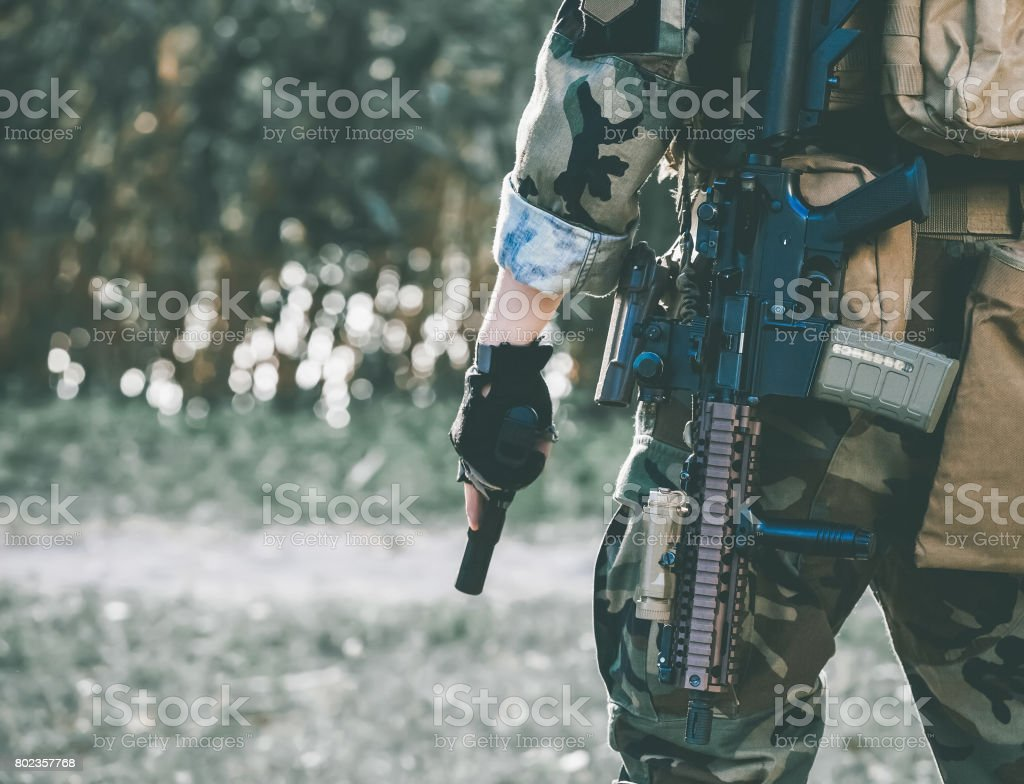 The soldier in the performance of tasks in camouflage and protective gloves holding a gun. stock photo