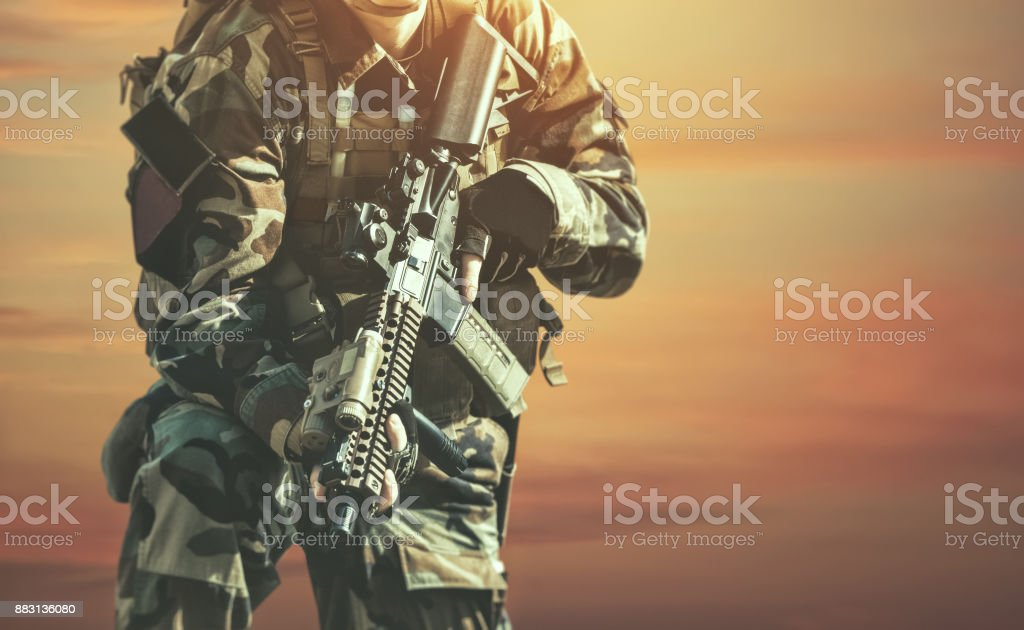 The soldier in the performance of tasks in camouflage and protective gloves holding a gun stock photo