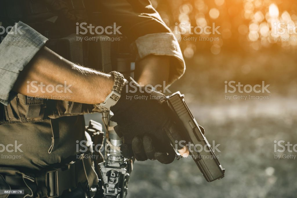 the soldier in the performance of tasks in camouflage and protective gloves holding a pistol. stock photo