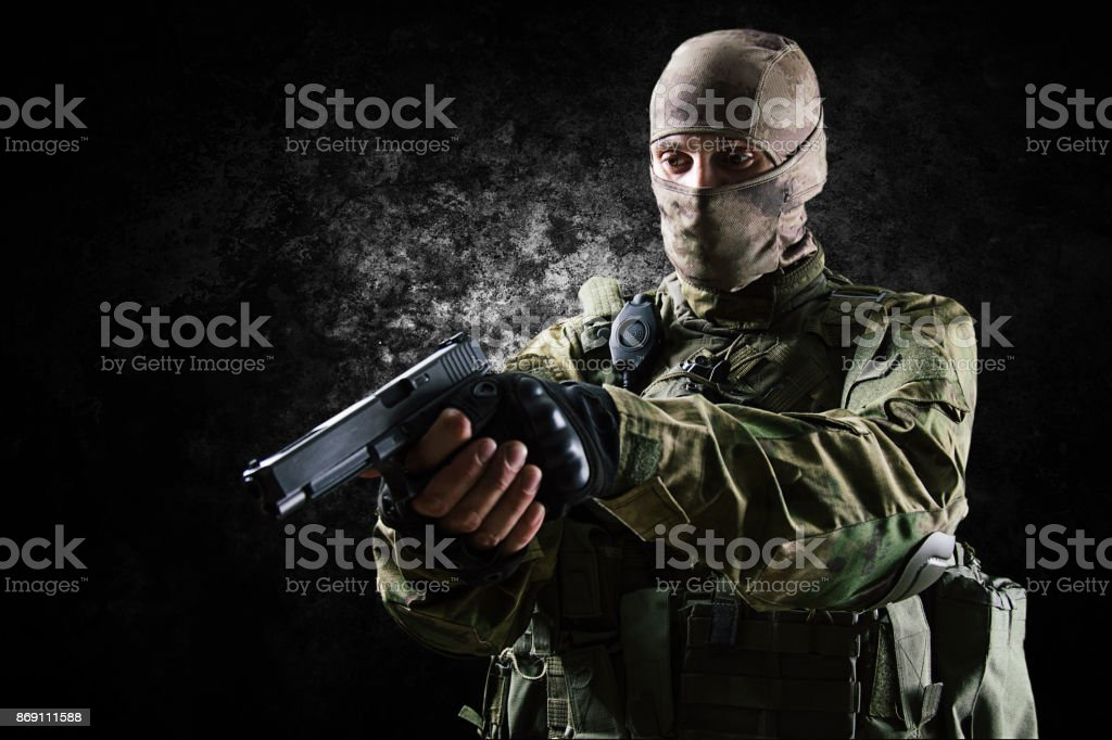 The soldier of the special unit in full equipment aims at the suspect from the pistol. stock photo