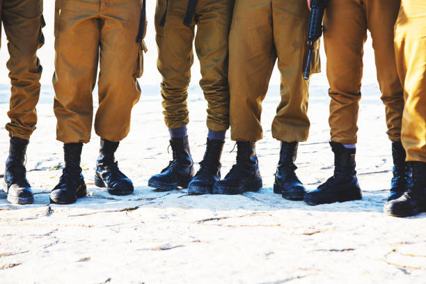 The soldier's footwear of the Israeli army which is put on legs in clear sunny day. stock photo