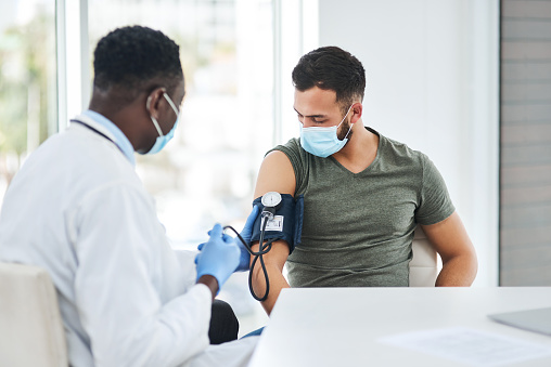 Shot of a doctor examining a young man with a blood pressure gauge