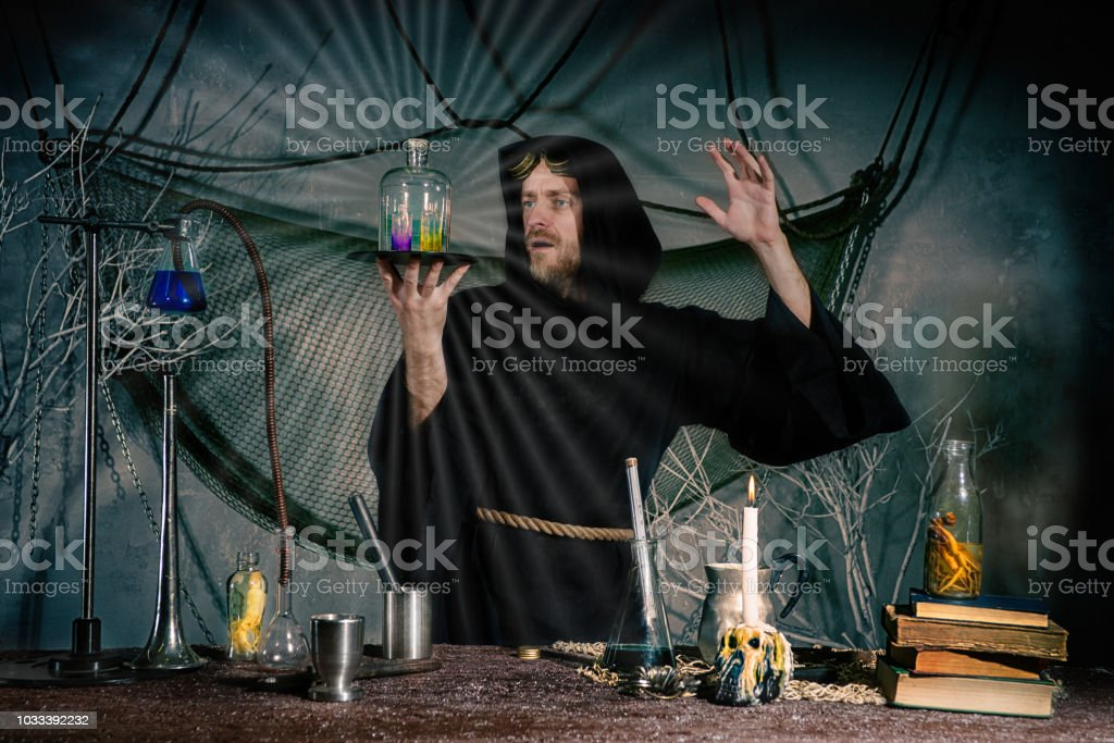 The sorcerer conducts a ritual to receive the elixir of eternal youth. Halloween stock photo