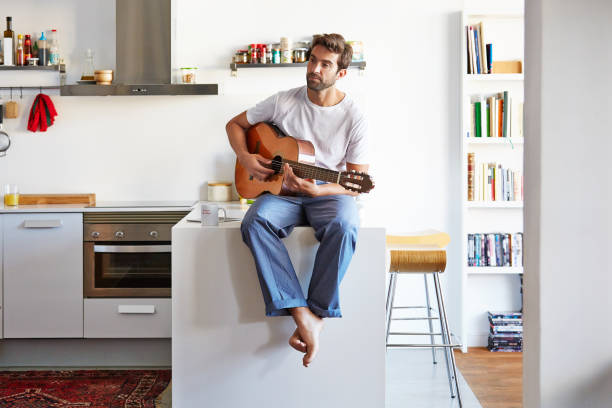 The soundtrack for the day Shot of a handsome young man playing the guitar in the morning at home bachelor stock pictures, royalty-free photos & images