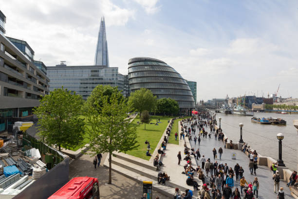 LONDON, UNITED KINGDOM  - MAY 15, 2015 - The Southbank with many people walking with City Hall and The Shard stock photo