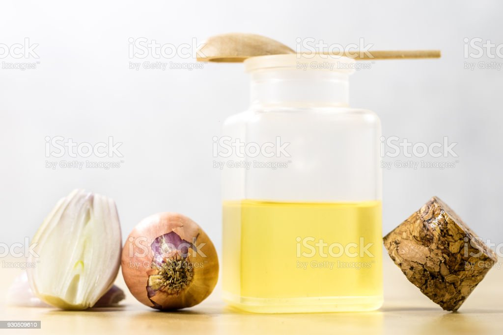 The specificity of onion on the flu. Healing juice in a vial on a wooden table. White background. stock photo
