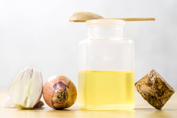 the specificity of onion on the flu. healing juice in a vial on a wooden table. white background. - onion juice stock photos and pictures