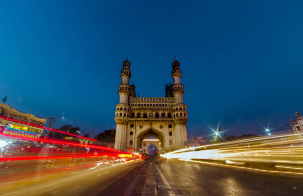 The Spectacular Char Minar during the blue hour Red and Yellow light trails cut across the charminar of Hyderabad as the sun dips down. char minar stock pictures, royalty-free photos & images