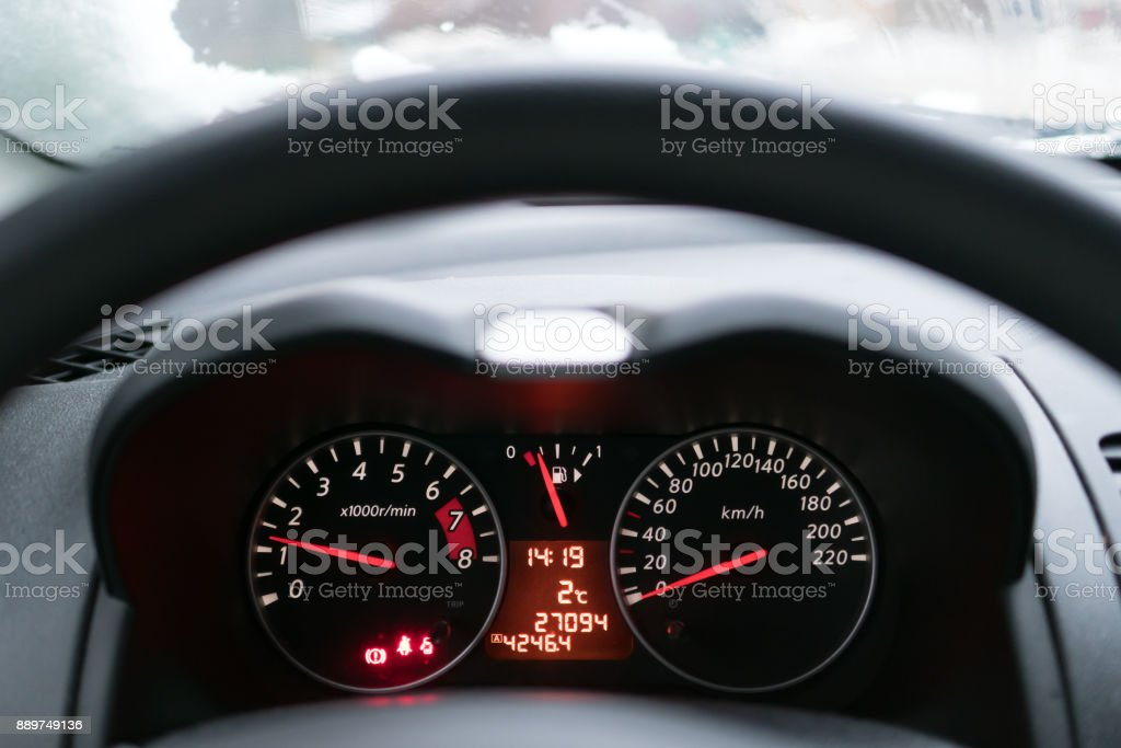 The speedometer in the car. From behind the steering wheel you can see how the red numbers on the scoreboard are glowing. stock photo