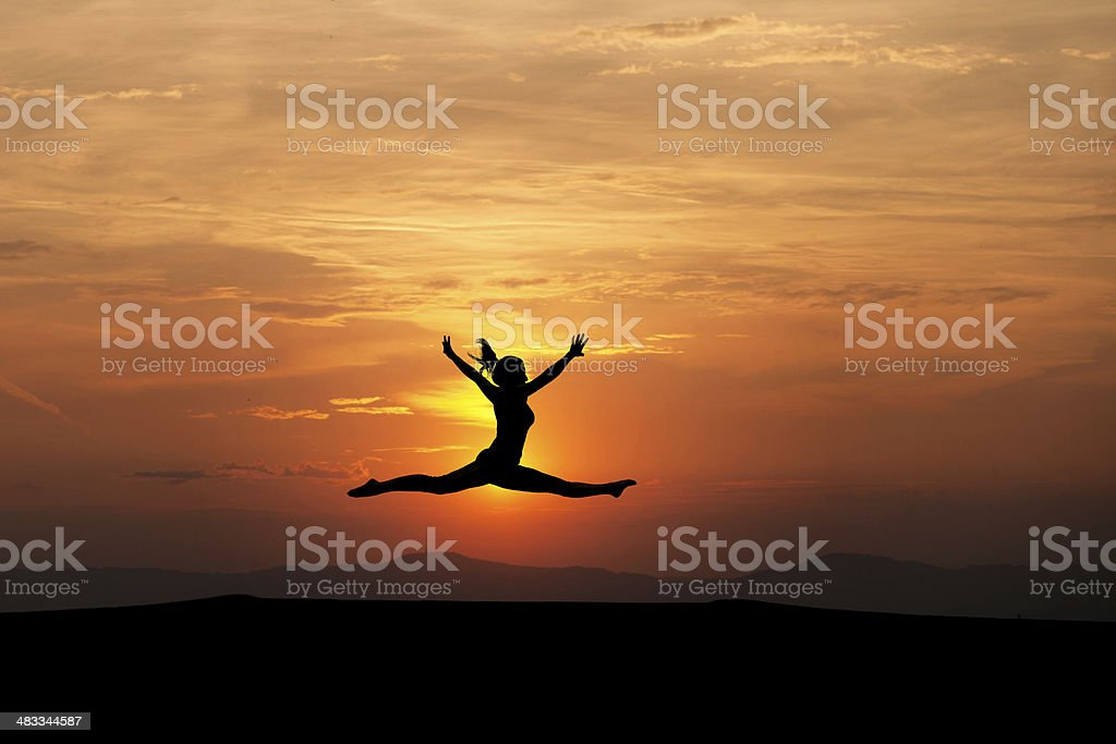 the splits by female gymnast in sunset stock photo