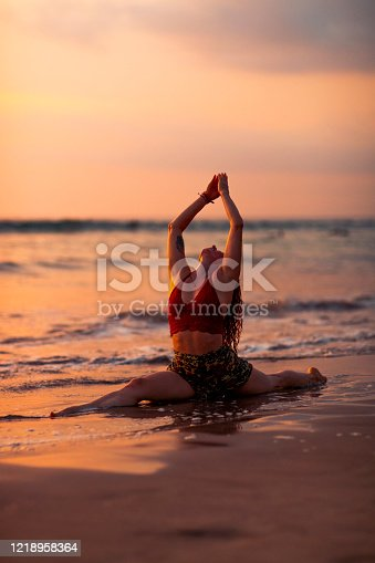 A mid adult woman doing the Hanumanasana pose as part of her yoga routine while on Kuta beach in Bali, Indonesia next to the sea. She is looking up to the sky with her arms raised.