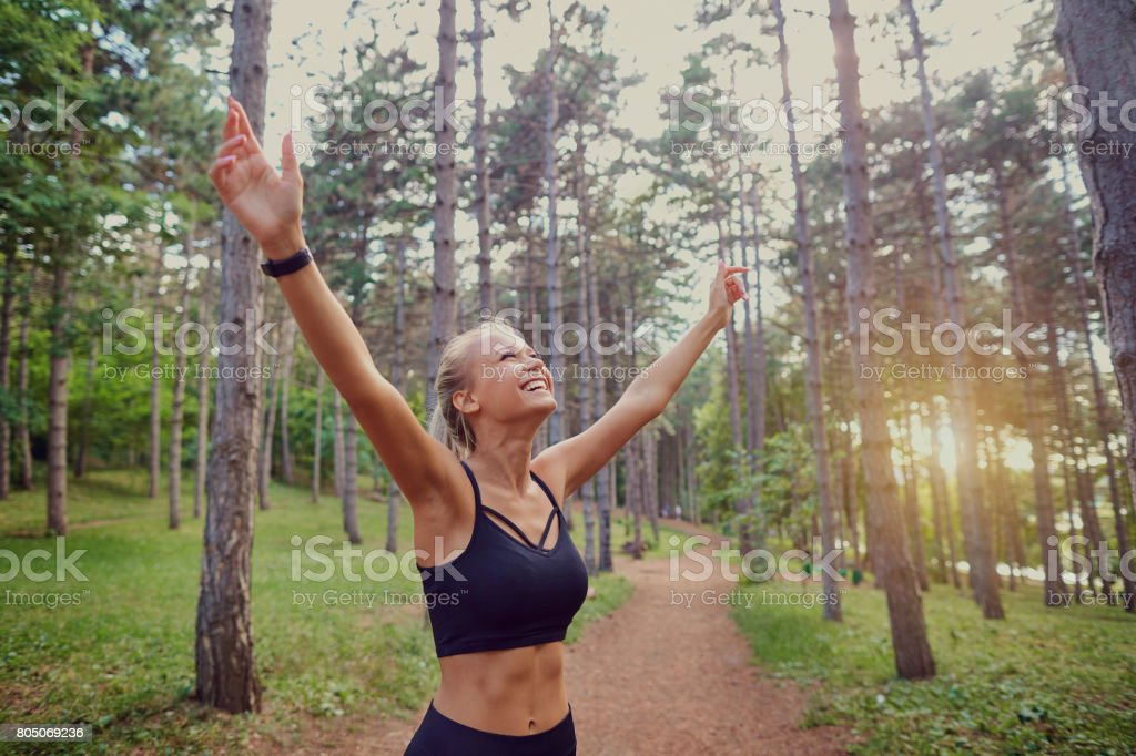 The sports girl her hands up in the forest. stock photo