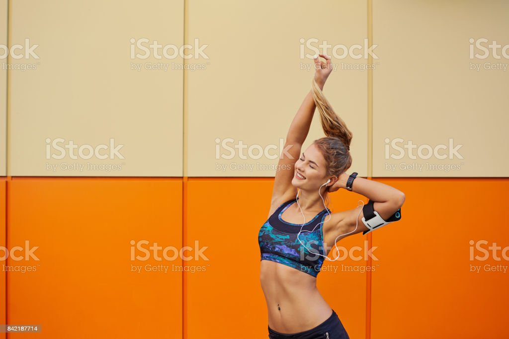The sports girl raised her hands up on an orange background. stock photo
