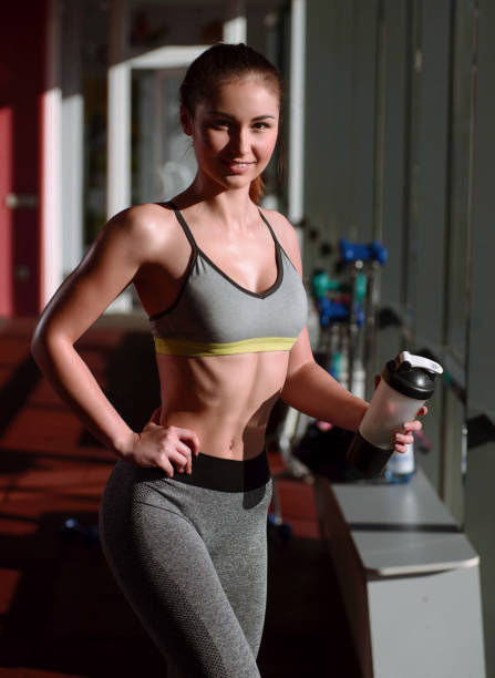 The sports young woman with protein cocktail in a shaker in a gym. Sports nutrition concept stock photo