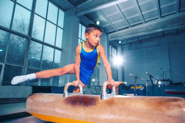 el deportista realiza el difícil ejercicio de gimnasia en el gimnasio. - gimnasia fotografías e imágenes de stock