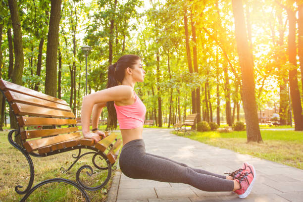 The sportswoman doing exercise in the park bench The sportswoman doing exercise in the park bench bicep stock pictures, royalty-free photos & images