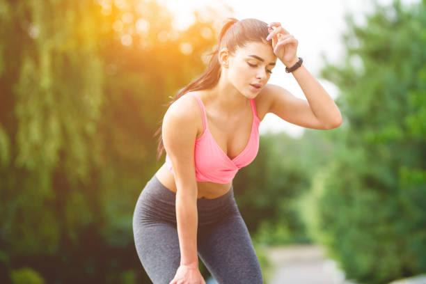 die sportlerin entspannt auf dem sonnenschein hintergrund - mit muskelkater trainieren stock-fotos und bilder