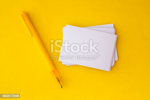 968272356istockphoto the stacking of mockup empty white business card with elegance pen  on vibrant yellow background , template for business  branding  design 950572948