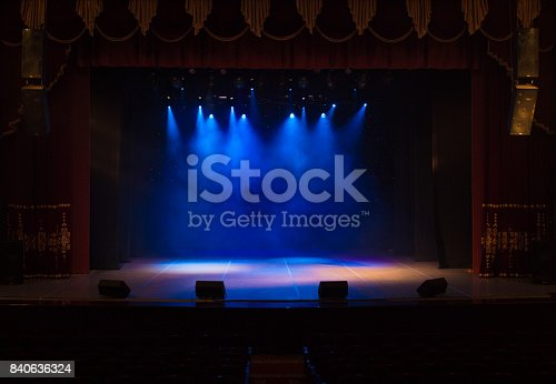 istock The stage of the theater illuminated by spotlights and smoke from the auditorium 840636324