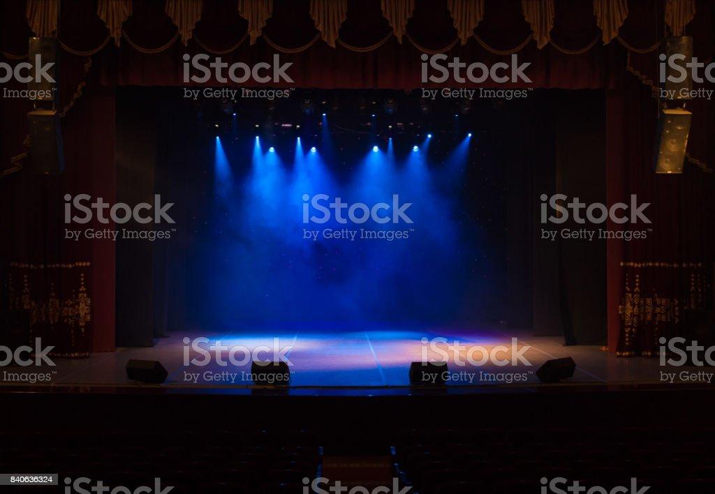 O palco do teatro iluminado por holofotes e fumaça do auditório - foto de acervo