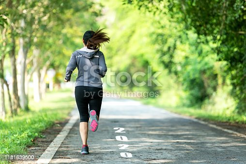 istock The start into the new year 2020. Start up of runner woman running on nature race track go to Goal of Success.  People running as part of Number 2020.  Holiday sport Concept 1181639500