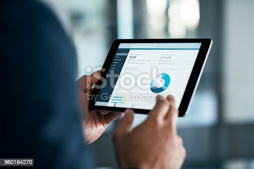 Closeup shot of a businessman analyzing statistics on a digital tablet in an office