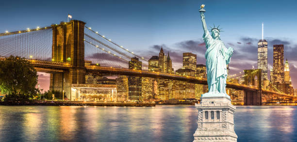 The Statue of Liberty and Brooklyn Bridge with World Trade Center background twilight sunset view, Landmarks of New York City stock photo