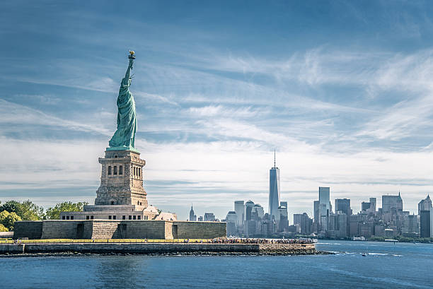 the statue of liberty and manhattan, new york city - international landmark stock photos and pictures