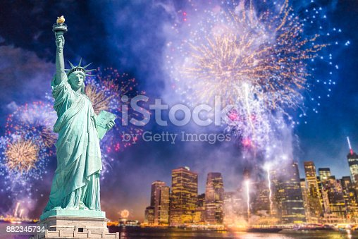 istock The Statue of Liberty with blurred background of cityscape with beautiful fireworks at night, Manhattan, New York City 882345734