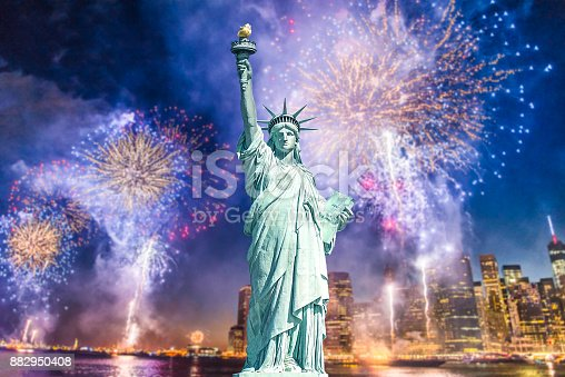 istock The Statue of Liberty with blurred background of cityscape with beautiful fireworks at night, Manhattan, New York City 882950408
