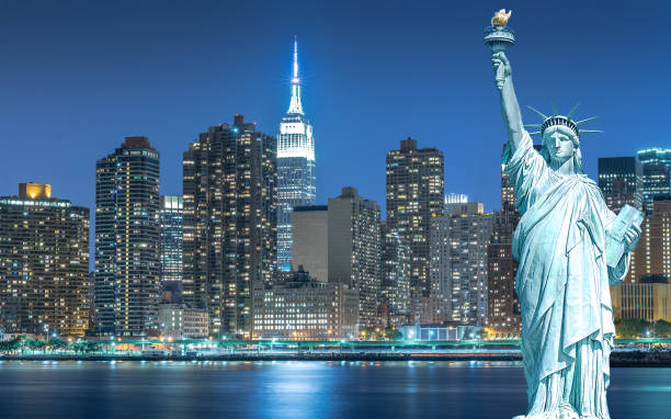 The Statue of Liberty with cityscape in Manhattan at night, New York City stock photo