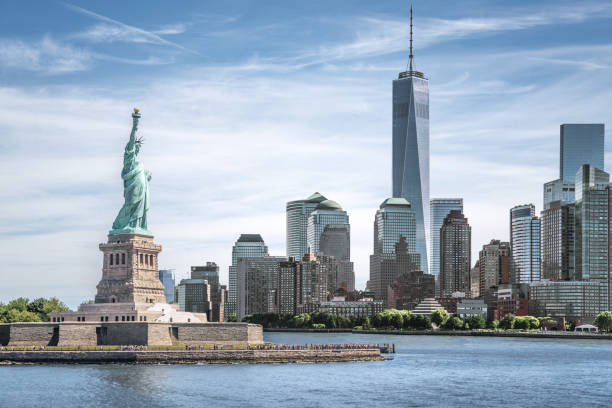 the statue of liberty with one world trade center background, landmarks of new york city - historic vs new stock photos and pictures