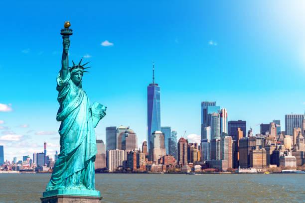 la statua della libertà con il centro di costruzione one world trade sul fiume hudson e sullo sfondo del paesaggio urbano di new york, punti di riferimento della città di new york. architettura e concetto di costruzione - mercato luogo per il commercio foto e immagini stock