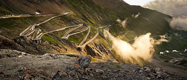 The Stelvio road Stilfser Joch - Passo dello Stelvio in the clouds at dawn. steep stock pictures, royalty-free photos & images