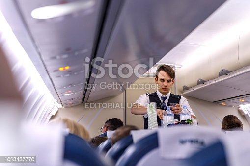 823006998 istock photo The steward serves passengers on board 1023437770