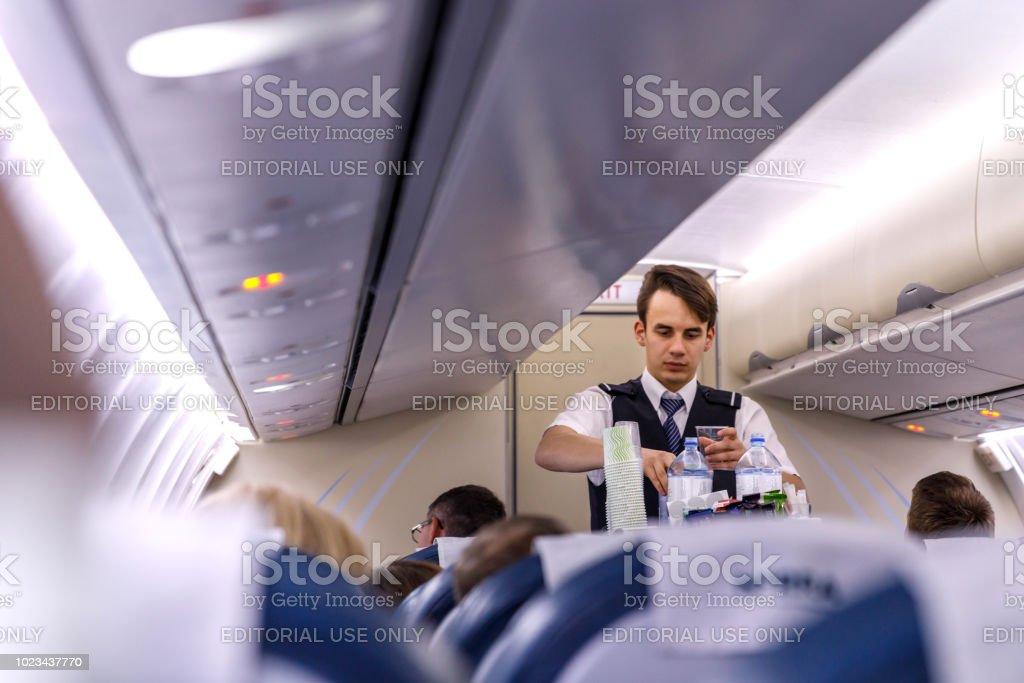 Der Steward dient Passagiere an Bord – Foto