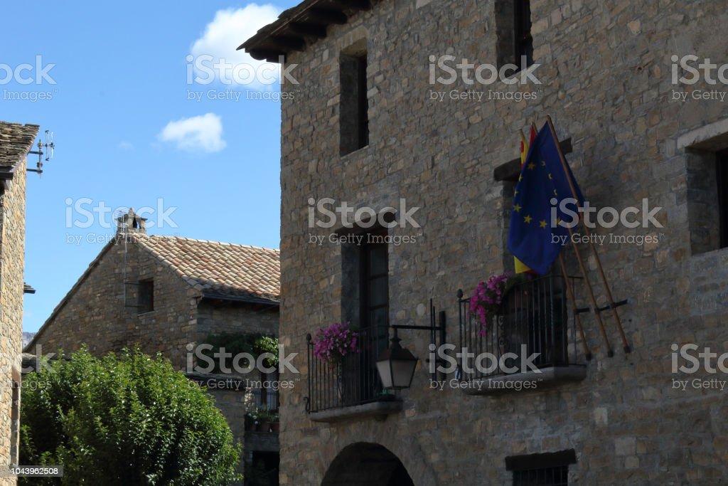 La piedra hizo pasillo de ciudad con las banderas Europea, española y aragonesa en la ciudad rural medieval Aínsa, situada en las montañas de Pirineos españoles - foto de stock